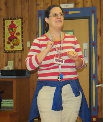 Lara Ravitch presenting in Russian language classroom wearing red and white striped shirt
