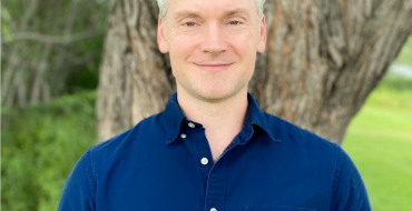 Peter Orte standing in front of tree wearing blue button down shirt.